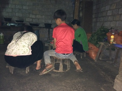 The children gather around the fire and chat whilst they help make dinner