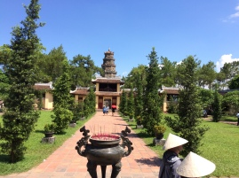 Tourists with their Vietnamese hats explore the Pagoda