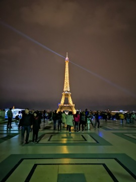 People gather to see the Eiffel Tower light up in a sparkling display